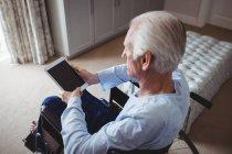 Homem idoso sentado em cadeira de rodas e usando tablet digital em casa — Fotografia de Stock