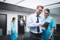 Médico y enfermera discutiendo sobre la tableta digital en el pasillo del hospital - foto de stock