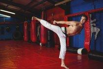 Каратист, практикующий кикбоксинг в фитнес-студии — стоковое фото