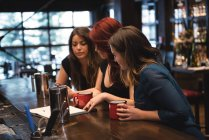 Friends holding coffee cups and looking at menu at bar counter — Stock Photo