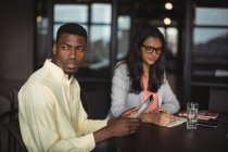 Бізнесмен проведення цифровий планшетний при колега написання примітки в офісі — стокове фото