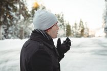 Thoughtful man smoking a cigarette in forest during winter — Stock Photo
