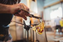Close-up of glassblower shaping a molten glass at glassblowing factory — Stock Photo