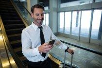 Бизнесмен на эскалаторе с помощью мобильного телефона в аэропорту — стоковое фото