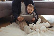 Padre y bebé con tableta digital en sala de estar en casa - foto de stock