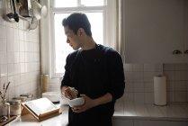 Mann mit Stößel und Mörser schaut auf digitales Tablet zu Hause — Stockfoto