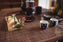 Sushi and cup of sake on table in restaurant — Stock Photo