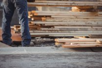 Low section of construction worker arranging timber at construction site — Stock Photo