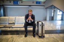 Empresário tenso sentado na área de espera com bagagem no terminal do aeroporto — Fotografia de Stock