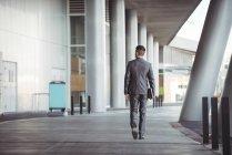 Vista posteriore dell'uomo d'affari con diario che cammina nel corridoio dell'edificio per uffici — Foto stock