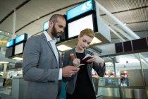 Ділових людей холдингу посадковий талон і використання мобільного телефону у терміналу аеропорту — стокове фото