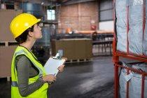 Побочный обзор уверенной женщины-работницы, изучающей продукцию на складе — стоковое фото