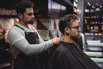 Barber putting cape over client in barber shop — Stock Photo