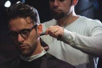 Uomo ottenere capelli tagliati da parrucchiere con trimmer in negozio di barbiere — Foto stock