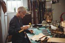 Зрелая ремесленница молотит кожей в мастерской — стоковое фото