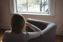 Rear view of woman sitting on sofa in living room at home — Stock Photo