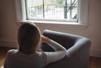 Вид сзади женщины, сидящей на диване в гостиной дома — стоковое фото