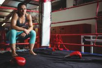 Thoughtful female boxer sitting on rope in boxing ring — Stock Photo