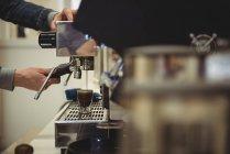Seção intermediária do homem preparando café no café — Fotografia de Stock
