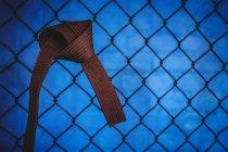 Крупный план коричневого пояса карате, висящего на сетке ограждения в фитнес-студии — стоковое фото