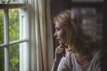 Beautiful woman looking through window at home — Stock Photo