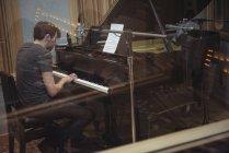 Homme jouant du piano dans un studio de musique — Photo de stock
