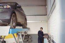 Mechanic using control box in repair garage — Stock Photo