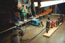 Крупный план крепления крепления лыж на лыжах с помощью дрели — стоковое фото