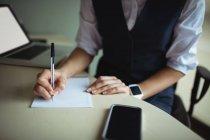 Бизнесвумен, пишущая на блокноте в офисе — стоковое фото