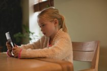 Ragazza carina utilizzando tablet digitale in soggiorno a casa — Foto stock