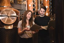Чоловік і жінка за допомогою цифрових планшетів і ноутбук у пивоварний завод — стокове фото