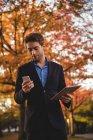 Empresário usando telefone celular e segurando tablet digital no outono — Fotografia de Stock
