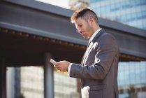 Empresário usando telefone celular perto do prédio de escritórios — Fotografia de Stock