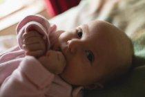 Крупный план милого ребенка, лежащего на кровати в спальне дома — стоковое фото