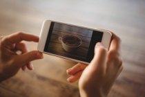 Женщина щелкает фото чашки кофе в кафе — стоковое фото