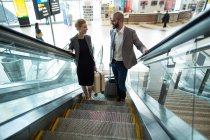 Pessoas de negócios interagindo uns com os outros, ao subir na escada rolante no terminal do Aeroporto — Fotografia de Stock