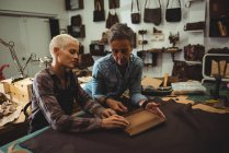 Craftswomen preparing leather cover for digital tablet — Stock Photo