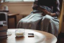 Frasco de vidro aberto e telefone móvel na mesa na sala de estar em casa — Fotografia de Stock
