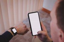 Мужчина исполнительный с помощью мобильного телефона и проверка времени на наручные часы в офисе — стоковое фото