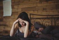 Femme bouleversée assise sur un lit pendant que l'homme dort en arrière-plan dans la chambre — Photo de stock
