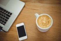 Close-up of coffee mug, mobile phone and laptop on wooden table — Stock Photo