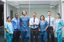 Portrait of smiling doctors standing together in corridor at hospital — Stock Photo