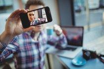 Молодой человек делает селфи с мобильного телефона в кафетерии — стоковое фото