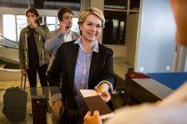 Деловая женщина вручает свой посадочный талон сотрудницам аэропорта — стоковое фото