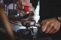 Крупный план официантки, использующей фальсификатор для прессования молотого кофе в портовый фильтр в кафе — стоковое фото