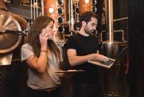 Людина, використовуючи ноутбук під час жінка, розмовляємо по телефону в пивоварного заводу — стокове фото