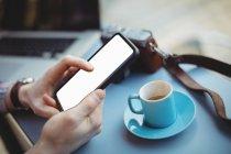 Mains de téléphone mobile mâle exécutif tenue tout en buvant le café à la cafétéria — Photo de stock