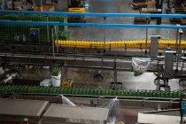 Высокий угол обзора бутылок на производственных линиях на соковом заводе — стоковое фото