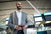 Smiling businessman holding a boarding pass and passport at airport terminal — Stock Photo