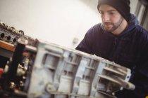 Mecânico verificando um carro peças na garagem de reparação — Fotografia de Stock
